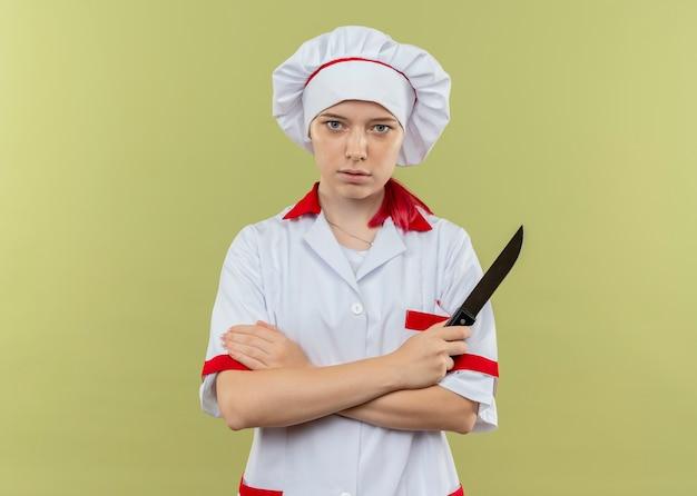 シェフの制服を着た若い自信を持って金髪の女性シェフが腕を組んで、緑の壁に孤立して見えるナイフを保持します