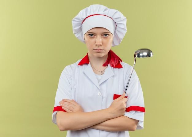 シェフの制服を着た若い自信を持って金髪の女性シェフが腕を組んで、緑の壁に隔離された取鍋を保持します。