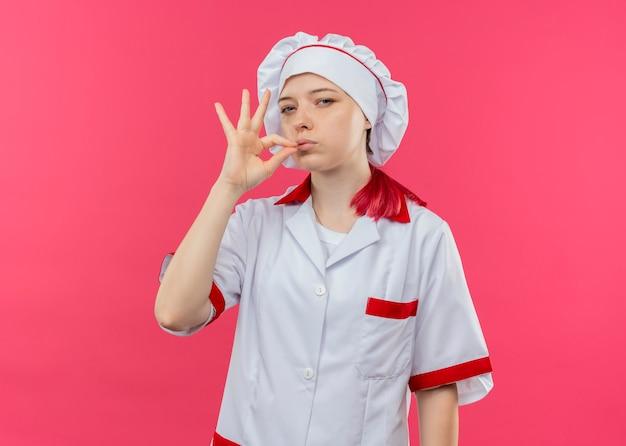 ピンクの壁に分離されたシェフの制服ジェスチャーおいしいサインで若い自信を持って金髪の女性シェフ