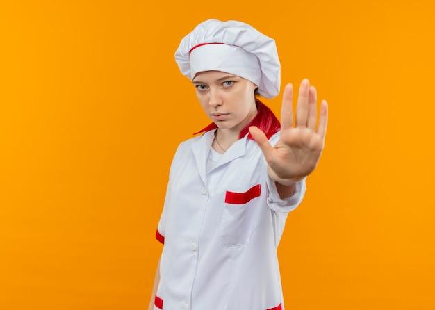 Молодая уверенная блондинка-шеф-повар в униформе шеф-повара жестами останавливает руку, изолированную на оранжевой стене