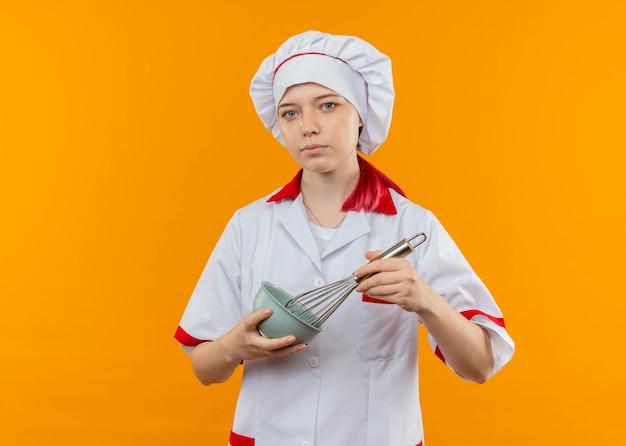 Молодая уверенная блондинка в униформе шеф-повара держит миску и венчик на оранжевой стене