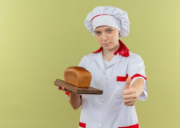 シェフの制服を着た若い自信を持って金髪の女性シェフはまな板にパンを保持し、緑の壁に隔離された親指を立てる