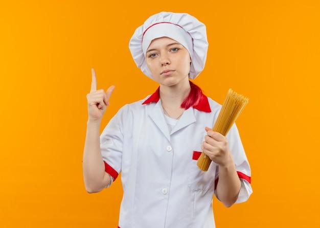 Молодая уверенная в себе блондинка-шеф-повар в форме шеф-повара держит кучу спагетти и указывает вверх, изолированную на оранжевой стене