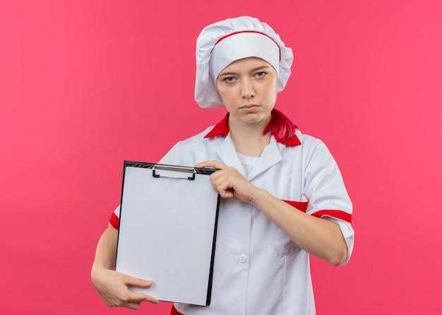 Молодая уверенная блондинка в униформе шеф-повара держит буфер обмена на розовой стене