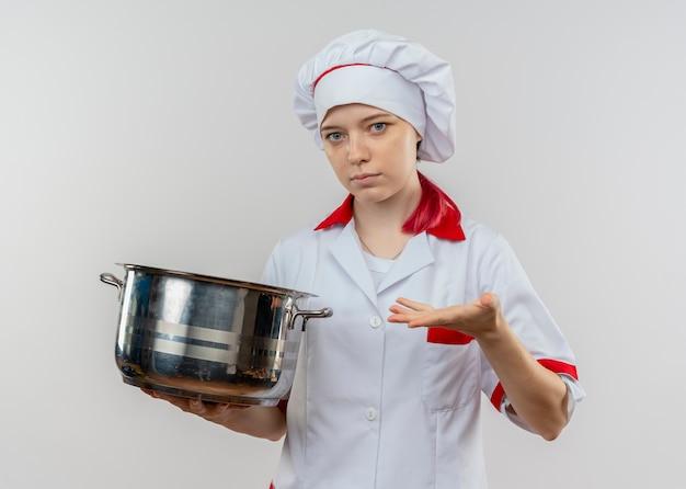 シェフの制服を着た若い自信を持って金髪の女性シェフは、白い壁に隔離された鍋を保持します