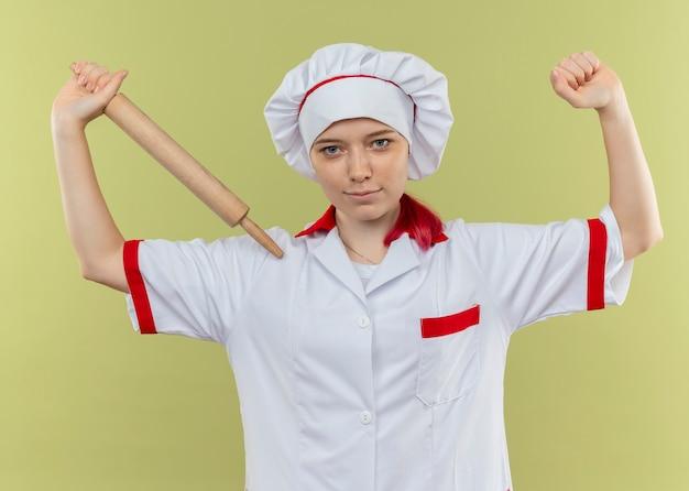シェフの制服を着た若い自信のある金髪の女性シェフは、麺棒を保持し、緑の壁に隔離された拳を上げます