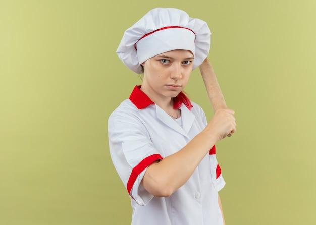 シェフの制服を着た若い自信を持って金髪の女性シェフは、麺棒を手に持って、緑の壁に孤立しているように見えます