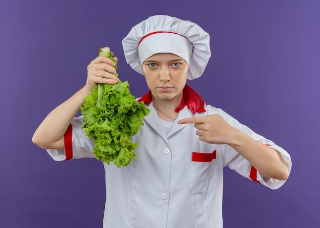 요리사 유니폼에 젊은 자신감 금발 여성 요리사는 샐러드를 거꾸로 보유하고 보라색 벽에 고립 된 손가락으로 포인트