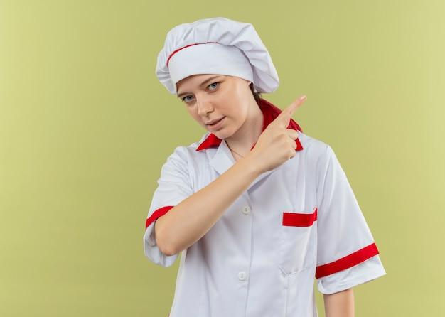 Молодая уверенная блондинка в униформе шеф-повара указывает в сторону и выглядит изолированной на зеленой стене