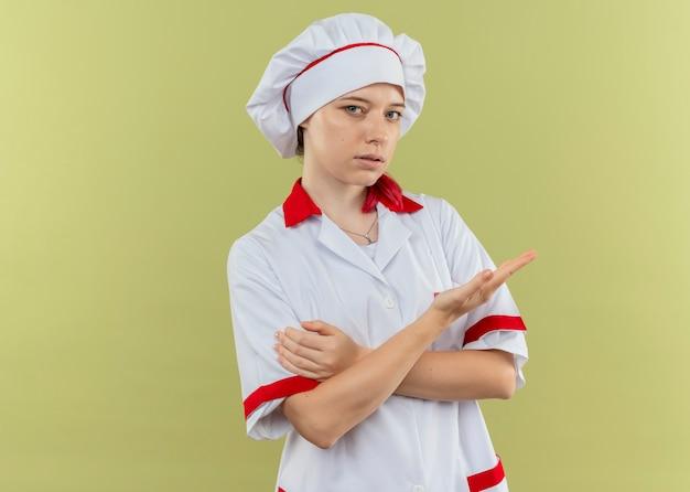 Молодая уверенная блондинка-шеф-повар в форме шеф-повара указывает на бок с рукой, изолированной на зеленой стене