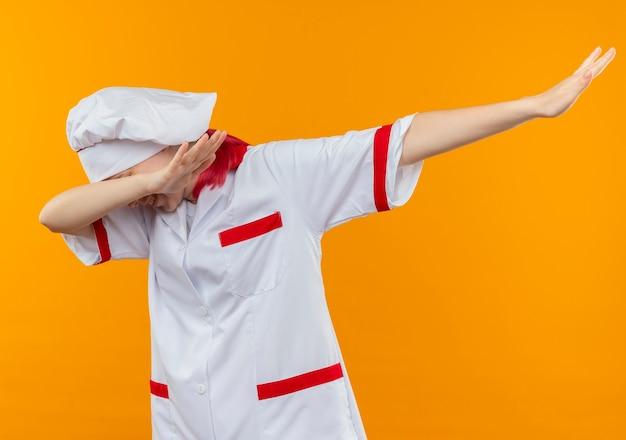シェフの制服を着た若い自信のある金髪の女性シェフは、オレンジ色の壁に孤立した軽くたたくふりをします