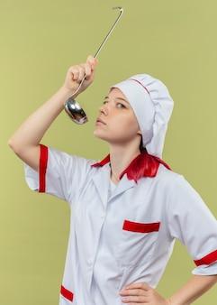 シェフの制服を着た若い自信のある金髪の女性シェフは、緑の壁に隔離された取鍋で試してみるふりをします