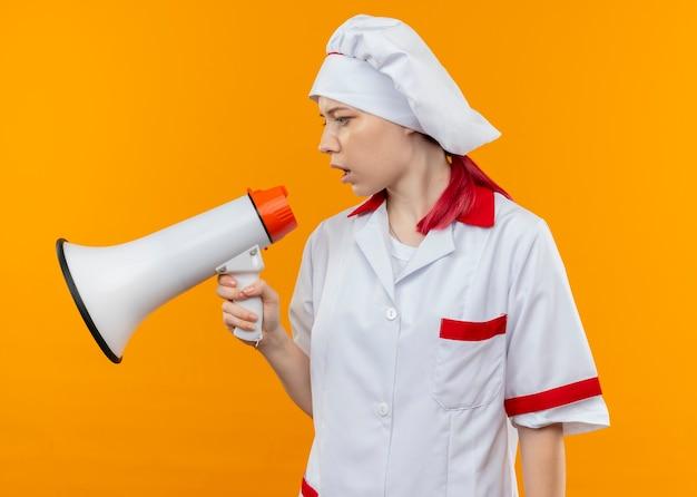 シェフの制服を着た若い自信を持って金髪の女性シェフがスピーカーを通して話し、オレンジ色の壁に隔離された側を見ます