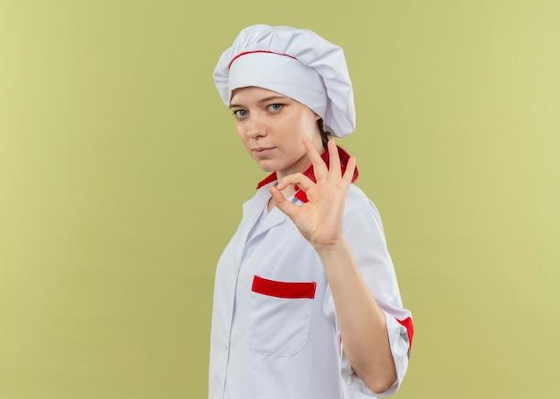 シェフの制服を着た若い自信を持って金髪の女性シェフが横に立って、緑の壁に隔離された手振りでok