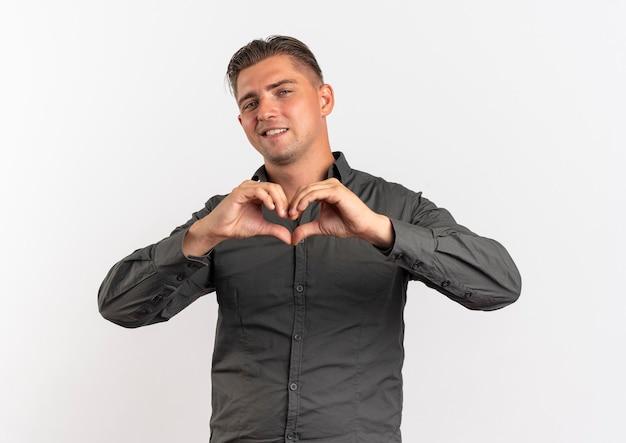 Giovane uomo bello biondo fiducioso gesti il segno della mano del cuore isolato su priorità bassa bianca con lo spazio della copia