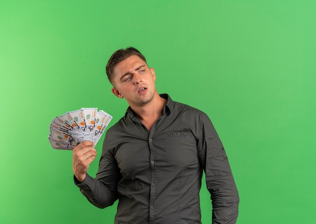 Young confident blonde handsome man holds money looking at side isolated on green space with copy space
