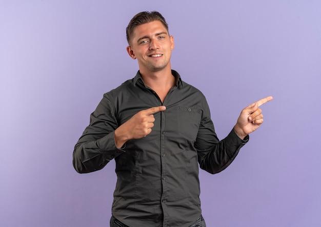 복사 공간 보라색 공간에 고립 된 측면에서 젊은 자신감 금발의 잘 생긴 남자 포인트
