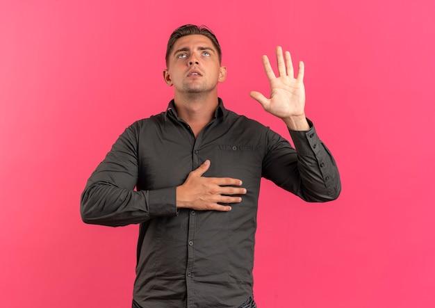 Giovane uomo bello biondo fiducioso alza la mano e mette sul petto isolato su sfondo rosa con spazio di copia