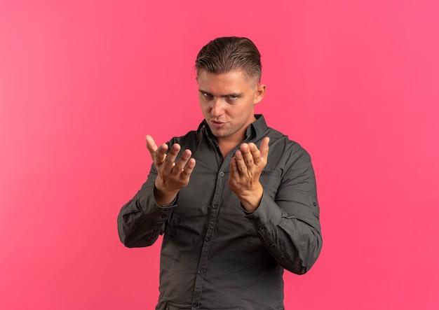 若い自信を持って金髪のハンサムな男は、コピースペースでピンクの背景に分離された手でキスを送信します。