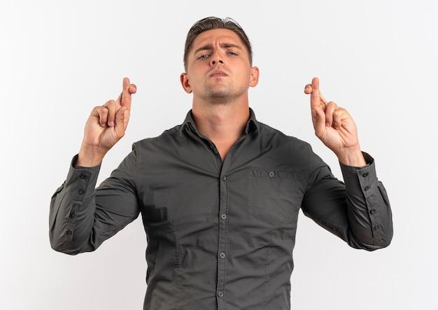젊은 자신감 금발의 잘 생긴 남자는 복사 공간이 흰색 공간에 고립 된 교차 손가락으로 약자