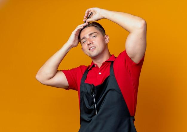 복사 공간 오렌지 공간에 고립 된 균일 한 빗질 머리에 젊은 자신감 금발 남성 이발사