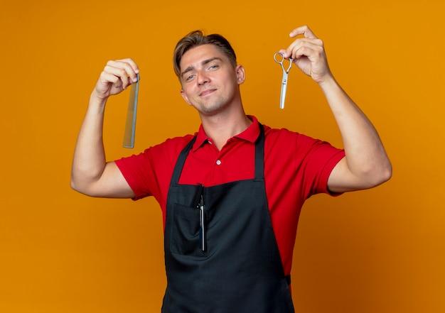 制服を着た若い自信のある金髪の男性の床屋は、櫛とはさみを逆さまに保持します