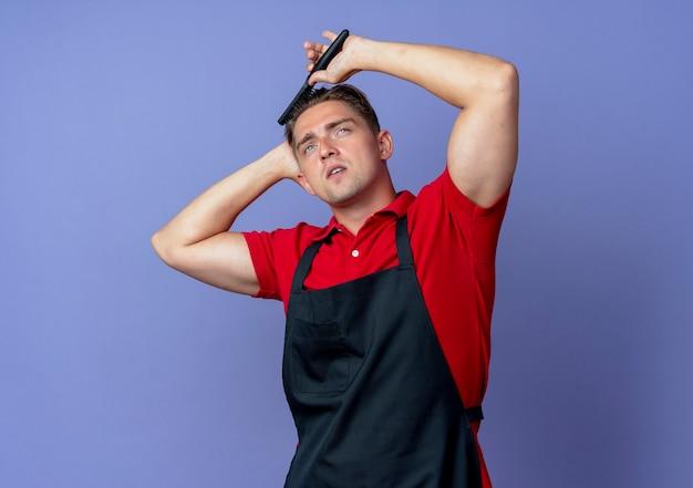 제복을 입은 젊은 자신감 금발 남성 이발사는 머리를 빗질하는 머리 뒤에 손을 넣습니다.