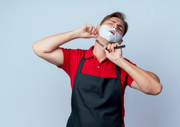 Молодой уверенный в себе светловолосый парикмахер в униформе смазал лицо пеной для бритья бритвой, изолированной на белом пространстве с копией пространства