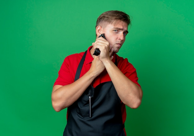 Young confident blonde male barber in uniform holds face trimming beard with hair clipper isolated on green space with copy space
