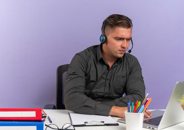 헤드폰에 젊은 자신감 금발 회사원 남자 복사 공간이 보라색 배경에 고립 된 노트북을보고 사무실 도구와 책상에 앉아