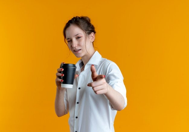 Молодая уверенная в себе русская блондинка моргает, держа чашку кофе и указывает на камеру, изолированную на оранжевом пространстве с копией пространства