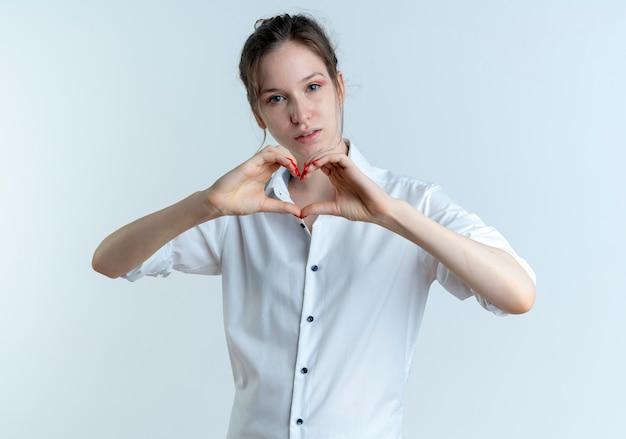 若い自信を持って金髪のロシアの女の子は、コピースペースで白いスペースに分離されたハートの手のサインをジェスチャーします。