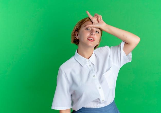 Молодая уверенная блондинка русская девушка жестикулирует знак проигравшего на зеленом фоне с копией пространства