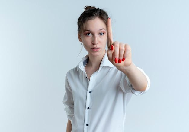Молодая уверенная блондинка русская девушка жестикулирует пальцем, изолированным на белом пространстве с копией пространства