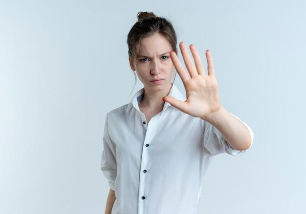 I giovani gesti biondi fiduciosi della ragazza russa fermano il segno della mano isolato su spazio bianco con lo spazio della copia