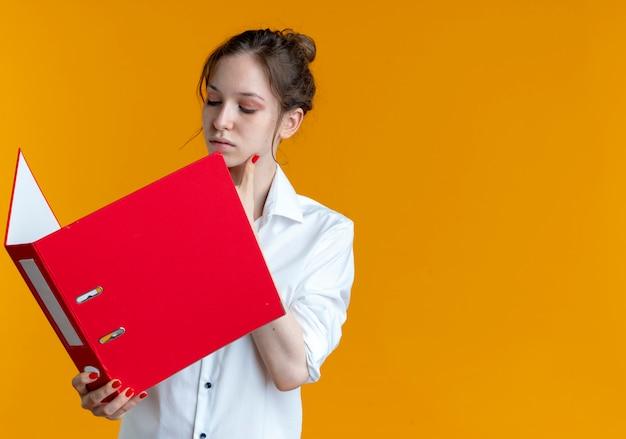 Молодая уверенная в себе русская блондинка держит и смотрит на папку с файлами
