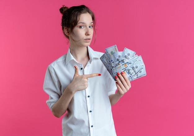 若い自信を持って金髪のロシアの女の子は、コピースペースでピンクのお金を保持し、ポイントします