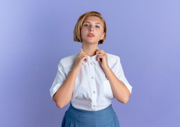 젊은 자신감 금발 러시아 여자 복사 공간이 보라색 배경에 고립 된 카메라를보고 칼라를 보유