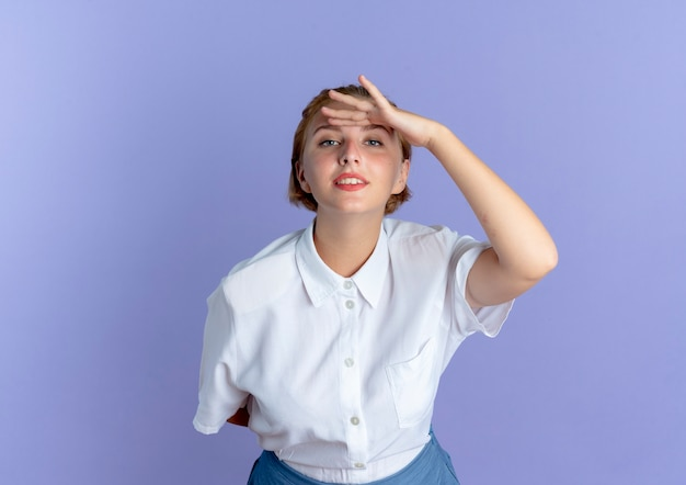 La giovane ragazza russa bionda fiduciosa tiene la mano a testa cercando di vedere isolato su sfondo viola con spazio di copia