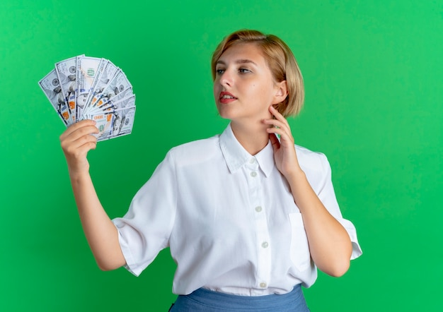 Young confident blonde russian girl holds and looks at money puts hand on neck isolated on green space with copy space