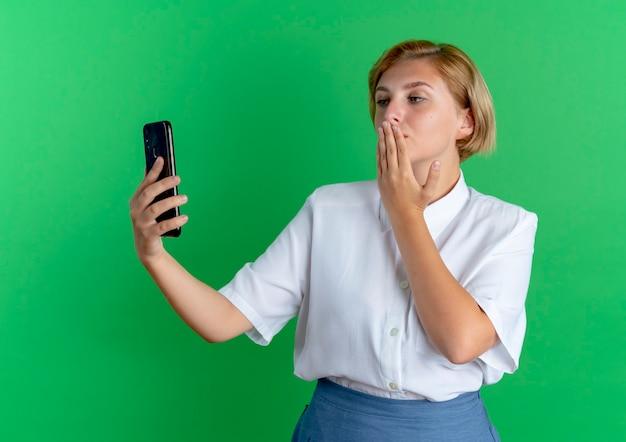 La giovane ragazza russa bionda fiduciosa tiene e guarda il telefono mette la mano sulla bocca isolata su fondo verde con lo spazio della copia