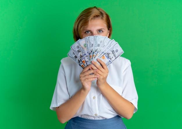젊은 자신감 금발 러시아 여자 복사 공간이 녹색 배경에 고립 된 돈을 통해 보인다