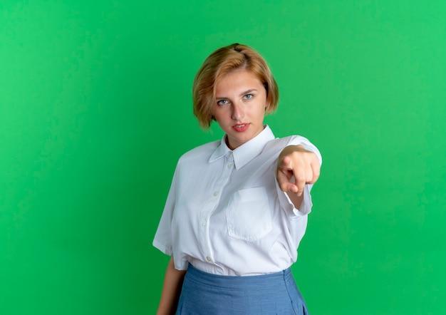 Молодая уверенная русская блондинка указывает на камеру, изолированную на зеленом фоне с копией пространства