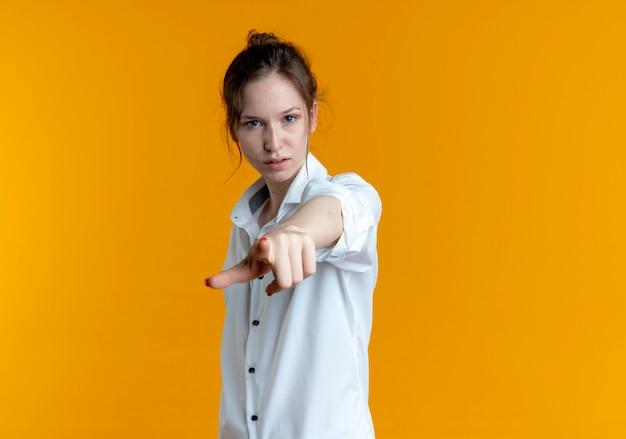 복사 공간 오렌지 공간에 고립 된 카메라에서 젊은 자신감 금발 러시아 여자 포인트