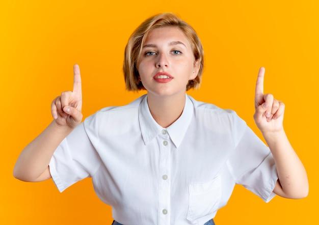 Молодая уверенная блондинка русская девушка указывает вверх на оранжевом фоне с копией пространства