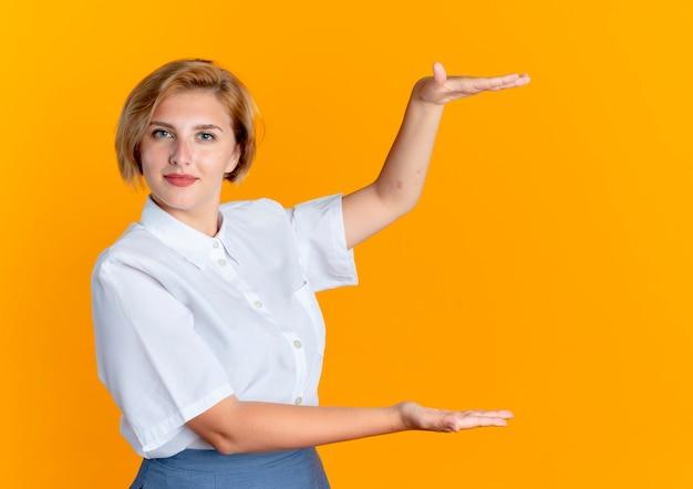 Giovane ragazza russa bionda fiduciosa finge di tenere qualcosa
