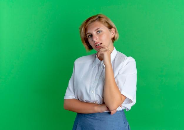 若い自信を持って金髪のロシアの女の子は、コピースペースで緑の背景に分離された唇に指を置きます