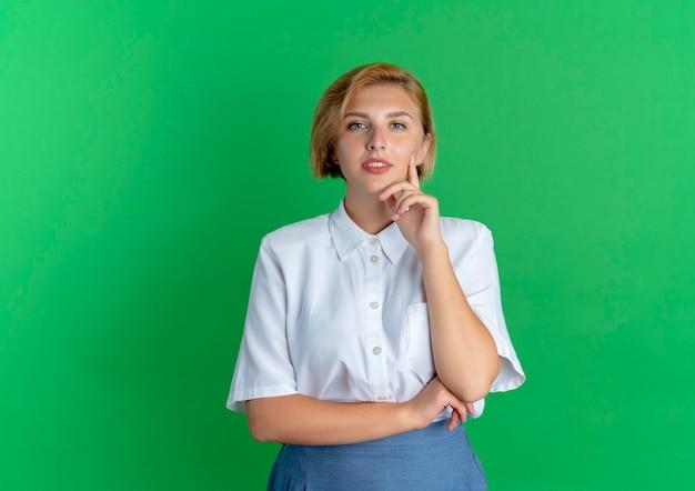 Молодая уверенная в себе белокурая русская девушка кладет руку на подбородок, глядя в камеру, изолированную на зеленом фоне с копией пространства