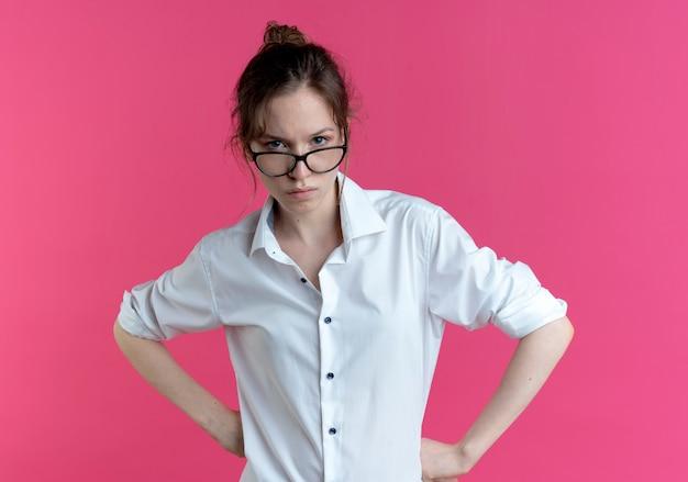 Молодая уверенная в себе русская блондинка в очках смотрит в камеру, изолированную на розовом пространстве с копией пространства
