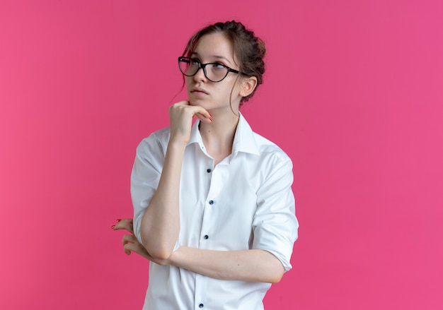 Young confident blonde russian girl with glasses puts hand on chin looking at side isolated on pink space with copy space